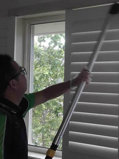 vacuum cleaning dust from window blinds